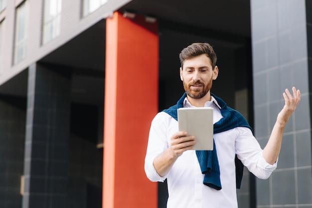 Selbstbewusster geschäftsmann in trendiger kleidung mit videoanruf auf digitalem tablet, während er in der nähe eines modernen bürogebäudes steht. konzept der konversation und technologie.