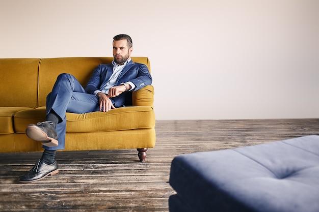 Selbstbewusster geschäftsmann, junger und attraktiver bärtiger mann in modischem anzug, entspannt sich auf