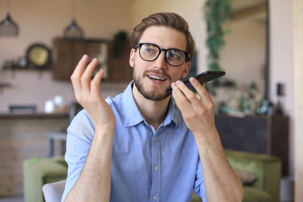 Selbstbewusster geschäftsmann mit brille, der smartphone in der nähe des mundes hält, um sprachnachrichten aufzunehmen oder den digitalen assistenten zu aktivieren.