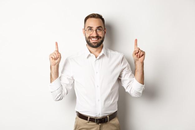 Selbstbewusster, gutaussehender geschäftsmann, der logo zeigt, auf die ankündigung zeigt und aufschaut und auf weißem hintergrund steht