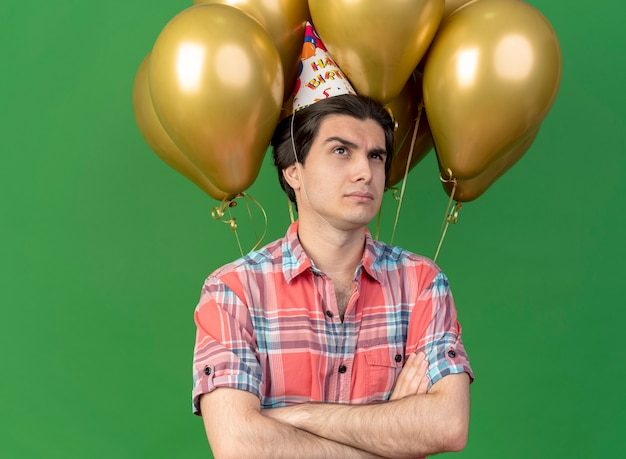 Selbstbewusster, gutaussehender kaukasier mit geburtstagsmütze steht mit verschränkten armen vor heliumballons balloon