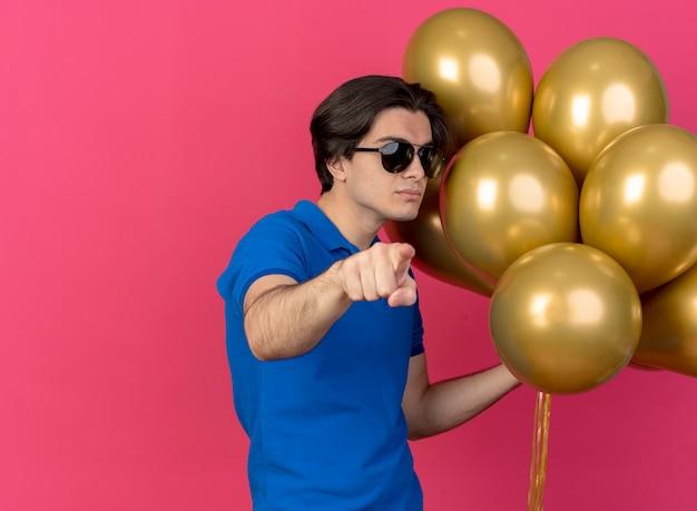 Selbstbewusster, gutaussehender kaukasier mit sonnenbrille hält heliumballons, die auf die kamera zeigen