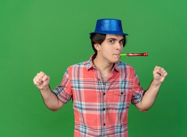 Selbstbewusster, gutaussehender kaukasischer mann mit blauem partyhut hält fäuste, die partypfeife blasen