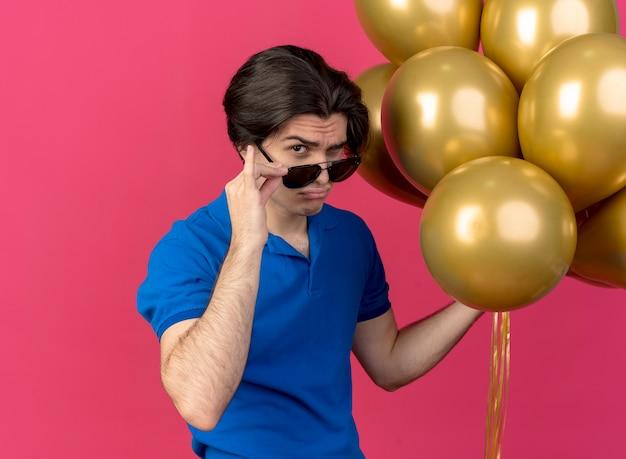 Selbstbewusster, gutaussehender kaukasischer mann mit sonnenbrille hält heliumballons mit blick in die kamera
