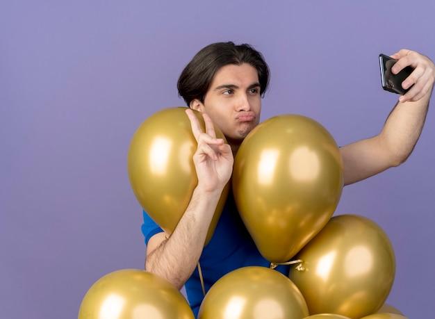 Selbstbewusster, gutaussehender kaukasischer mann steht mit heliumballons, die das sieghandzeichen gestikulieren und das telefon beim selfie betrachten