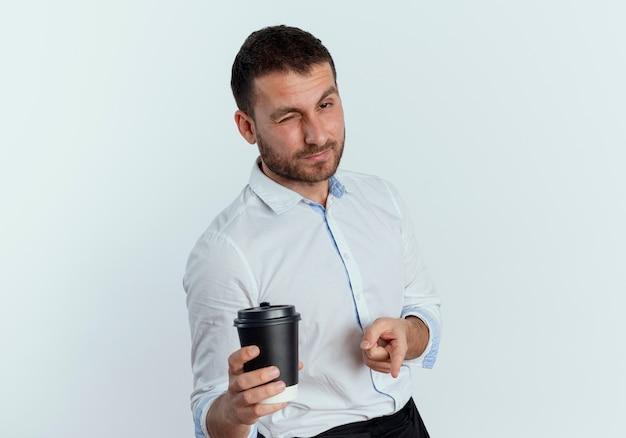 Selbstbewusster gutaussehender mann blinzelt auge, das kaffeetasse hält und lokalisiert auf weiße wand zeigt