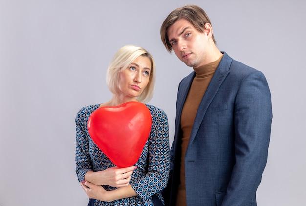 Selbstbewusster, gutaussehender mann, der am valentinstag mit einer hübschen blonden frau steht, die einen roten herzballon hält