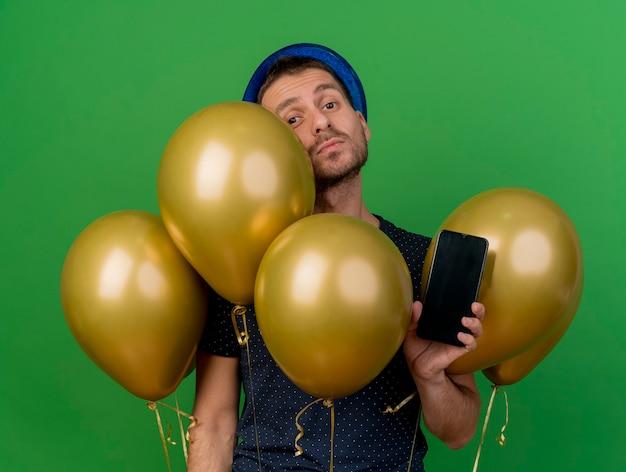 Selbstbewusster gutaussehender mann, der blauen parteihut trägt, steht mit heliumballons und hält telefon lokalisiert auf grüner wand