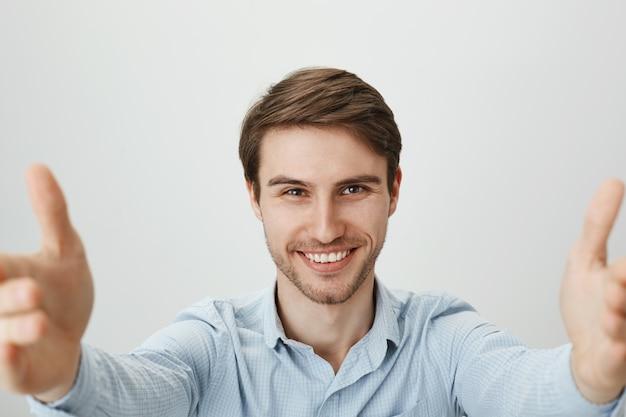 Selbstbewusster gutaussehender mann, der selfie oder videoanruf mit digitalem tablett nimmt