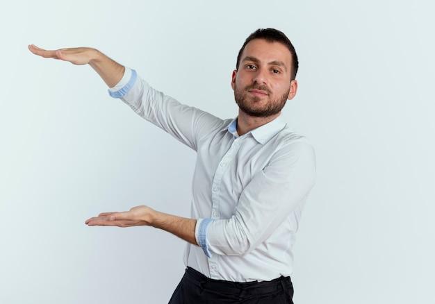 Selbstbewusster gutaussehender mann gibt vor, etwas isoliert auf weißer wand zu halten