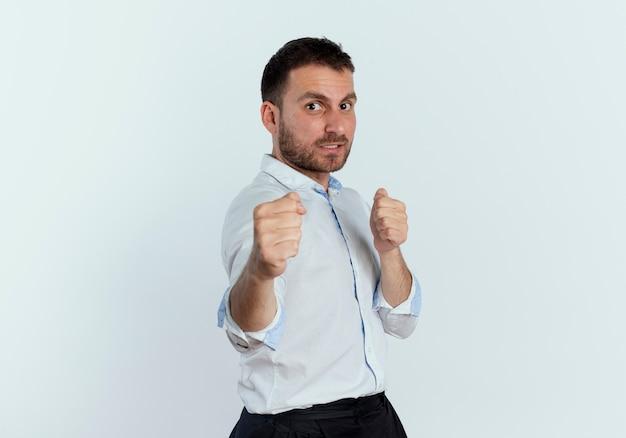 Selbstbewusster gutaussehender mann hält fäuste bereit, isoliert auf weiße wand zu schlagen