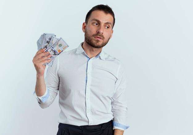 Selbstbewusster gutaussehender mann hält geld, das seite betrachtet, die auf weißer wand lokalisiert wird