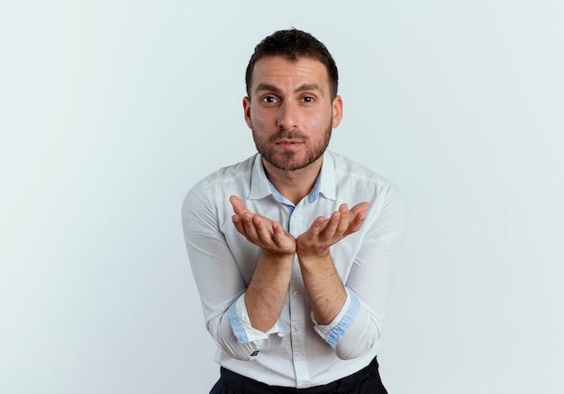 Selbstbewusster gutaussehender mann hält hände zusammen und schaut isoliert auf weißer wand