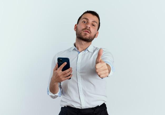 Selbstbewusster gutaussehender mann hält telefon und daumen auf weißer wand isoliert