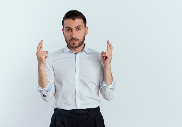 Selbstbewusster gutaussehender mann kreuzt finger, die isoliert auf weißer wand schauen