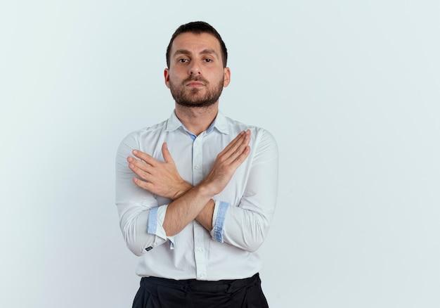 Selbstbewusster gutaussehender mann kreuzt hände, die kein zeichen zeigen, das auf weißer wand isoliert wird