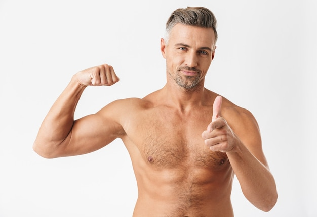 Selbstbewusster, gutaussehender mann mit nacktem oberkörper, der isoliert auf weißem steht und bizeps beugt