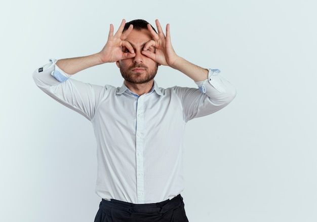 Selbstbewusster gutaussehender mann schaut durch finger, die auf weißer wand isoliert werden
