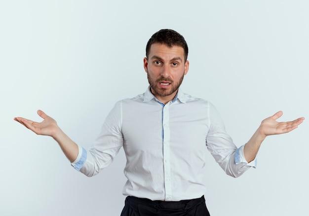 Selbstbewusster gutaussehender mann steht mit offenen händen lokalisiert auf weißer wand