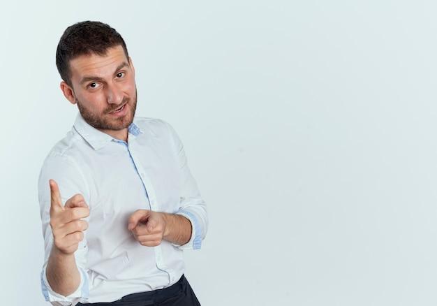 Selbstbewusster gutaussehender mann zeigt mit zwei händen lokalisiert auf weißer wand
