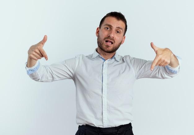 Selbstbewusster gutaussehender mann zeigt nach unten mit zwei händen, die auf weißer wand isoliert werden