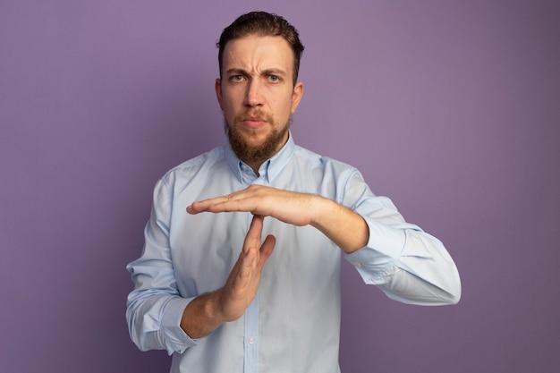 Selbstbewusster hübscher blonder mann gestikuliert auszeitzeichen lokalisiert auf lila wand
