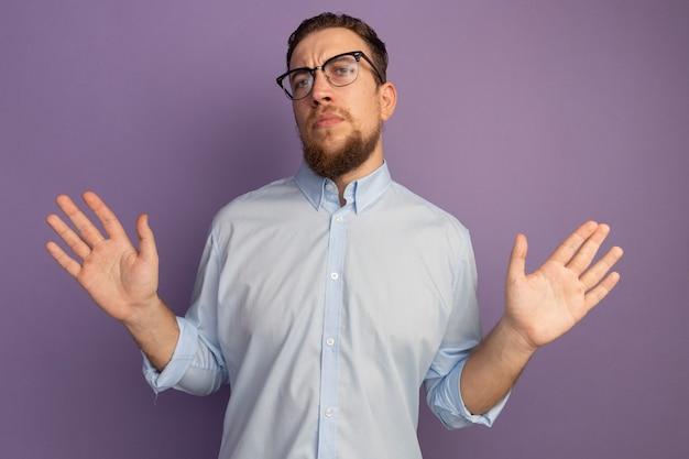 Selbstbewusster hübscher blonder mann in der optischen brille steht mit erhobenen händen, die auf lila wand lokalisiert werden