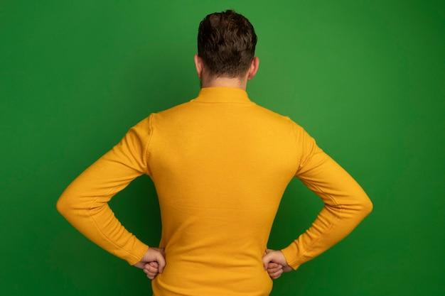Selbstbewusster hübscher blonder mann steht mit dem rücken zur kamera, die hände auf taille isoliert setzt