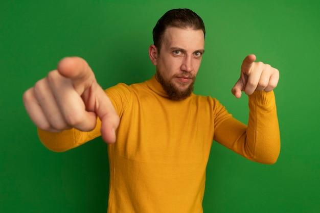 Selbstbewusster hübscher blonder mann zeigt mit zwei händen auf grün auf kamera