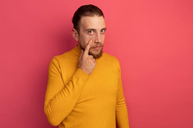Selbstbewusster hübscher blonder mann zieht augenlid auf rosa herunter