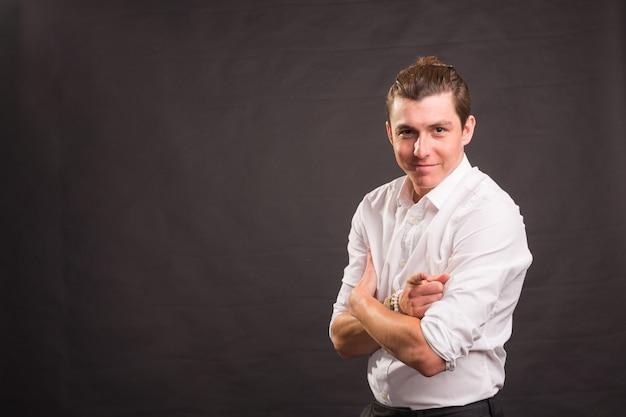 Selbstbewusster hübscher mann im weißen hemd, das finger auf kamera auf einer schwarzen wand mit kopienraum zeigt.
