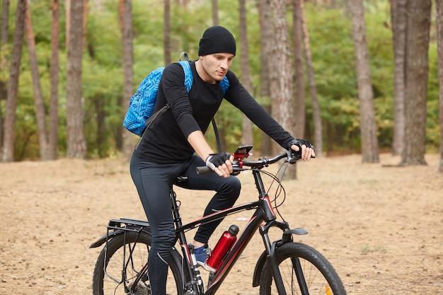 Selbstbewusster hübscher radfahrer, der sein fahrrad im herbstwald fährt, seinem weg folgt, karte auf seinem smartphone hat, schwarze sportbekleidung trägt