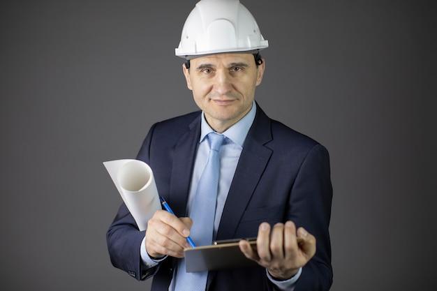 Selbstbewusster ingenieur im schutzhelm mit zwischenablage und blaupausenrolle