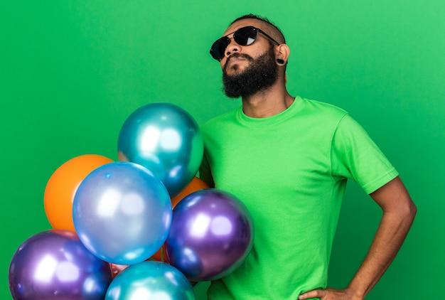 Selbstbewusster junger afroamerikaner mit brille, der luftballons hält, die hand auf die hüfte legen