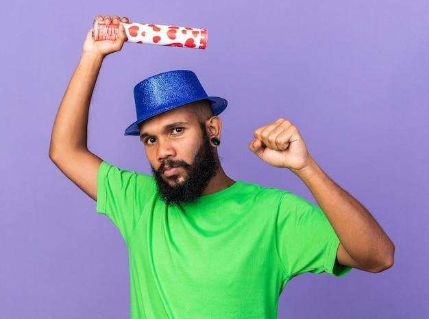 Selbstbewusster junger afroamerikaner mit partyhut, der konfettikanonen hält und ja-geste zeigt