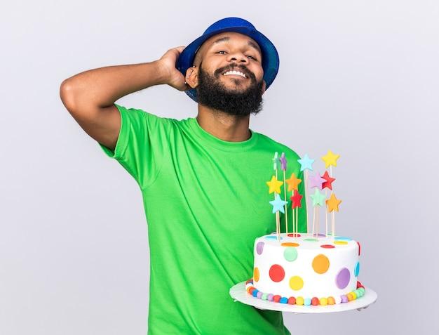 Selbstbewusster junger afroamerikaner mit partyhut, der kuchen isoliert auf weißer wand hält