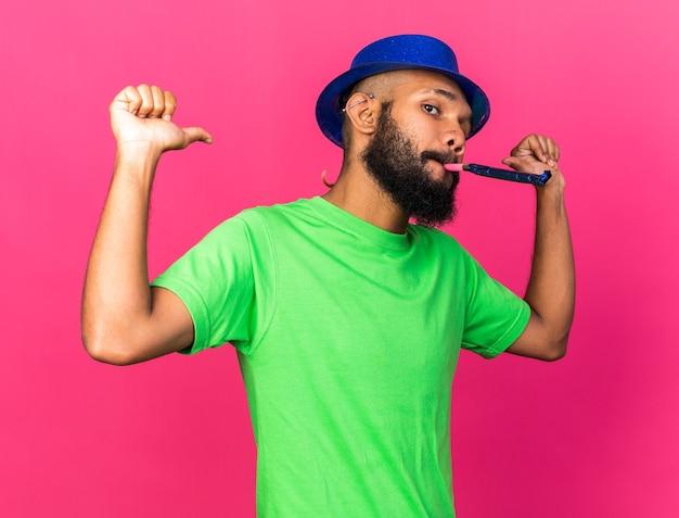 Selbstbewusster junger afroamerikaner mit partyhut, der partypfeife bläst, zeigt auf sich selbst at