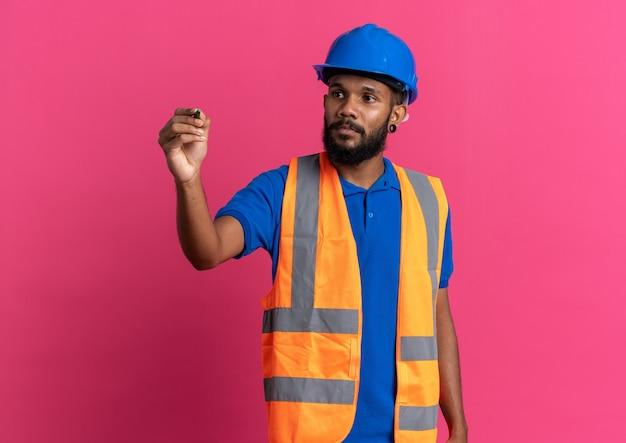 Selbstbewusster junger afroamerikanischer baumeister in uniform mit schutzhelm, der den stift auf rosafarbenem hintergrund mit kopienraum isoliert hält und betrachtet