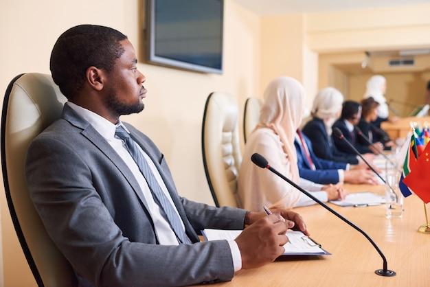 Selbstbewusster junger afroamerikanischer delegierter in abendgarderobe, der mit ausländischen kollegen auf der konferenz am tisch sitzt