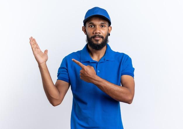 Selbstbewusster junger afroamerikanischer lieferbote, der auf seine hand zeigt, die auf weißer wand mit kopienraum isoliert ist?