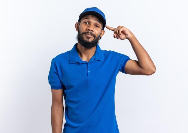 Selbstbewusster junger afroamerikanischer lieferbote, der auf seine mütze zeigt, die auf weißer wand mit kopienraum isoliert ist?
