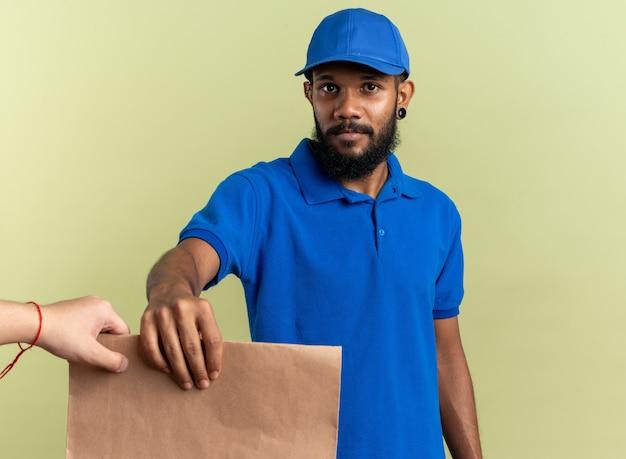 Selbstbewusster junger afroamerikanischer lieferbote, der jemandem, der auf einer olivgrünen wand mit kopienraum isoliert ist, ein lebensmittelpaket gibt