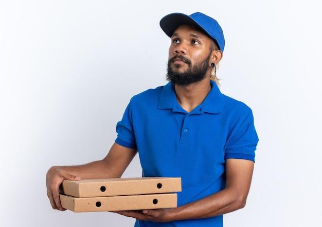 Selbstbewusster junger afroamerikanischer lieferbote, der pizzakartons hält und die seite isoliert auf weißem hintergrund mit kopienraum betrachtet