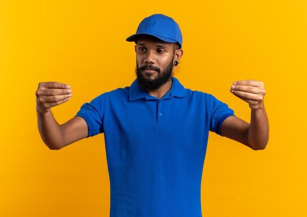 Selbstbewusster junger afroamerikanischer lieferbote, der vorgibt, etwas isoliert auf oranger wand mit kopierraum zu halten