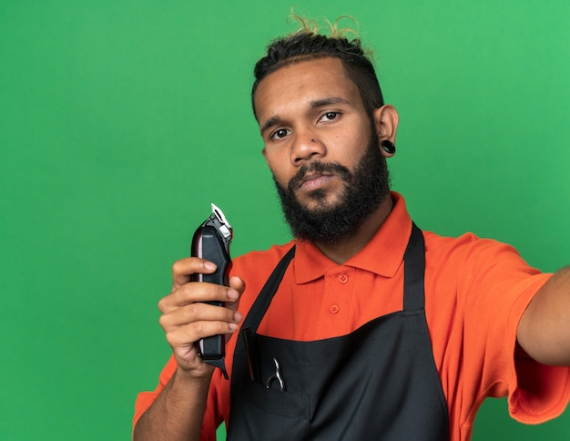 Selbstbewusster junger afroamerikanischer männlicher friseur, der uniform trägt und die hand in richtung kamera ausstreckt, die haarschneidemaschinen isoliert auf grüner wand hält