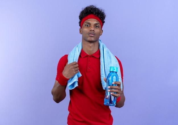 Selbstbewusster junger afroamerikanischer sportlicher mann mit stirnband und armband, der eine wasserflasche mit handtuch auf der schulter hält