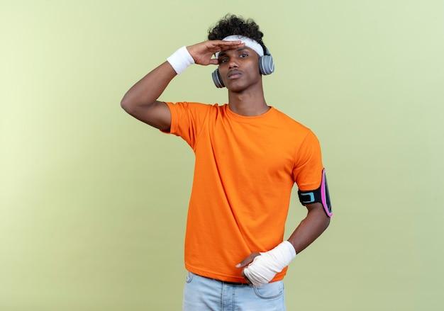Selbstbewusster junger afroamerikanischer sportlicher mann mit stirnband und armband und telefonarmband mit kopfhörern, die mit der hand aussehen