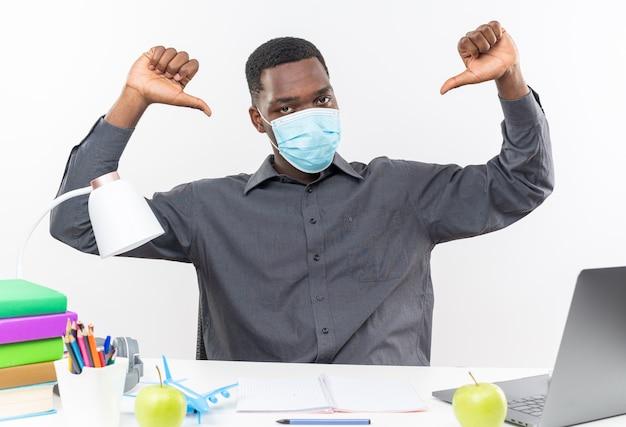 Selbstbewusster junger afroamerikanischer student, der eine medizinische maske trägt und am schreibtisch sitzt, mit schulwerkzeugen, die auf sich selbst zeigen