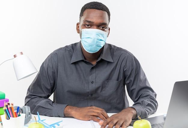 Selbstbewusster junger afroamerikanischer student mit medizinischer maske, der mit schulwerkzeugen am schreibtisch sitzt