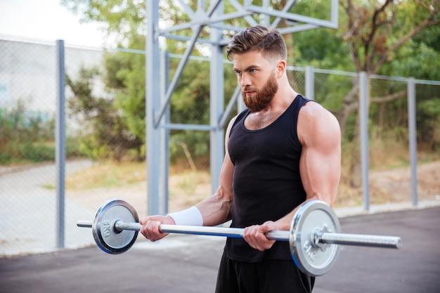 Selbstbewusster junger bärtiger fitness-mann, der draußen übungen mit der langhantel macht